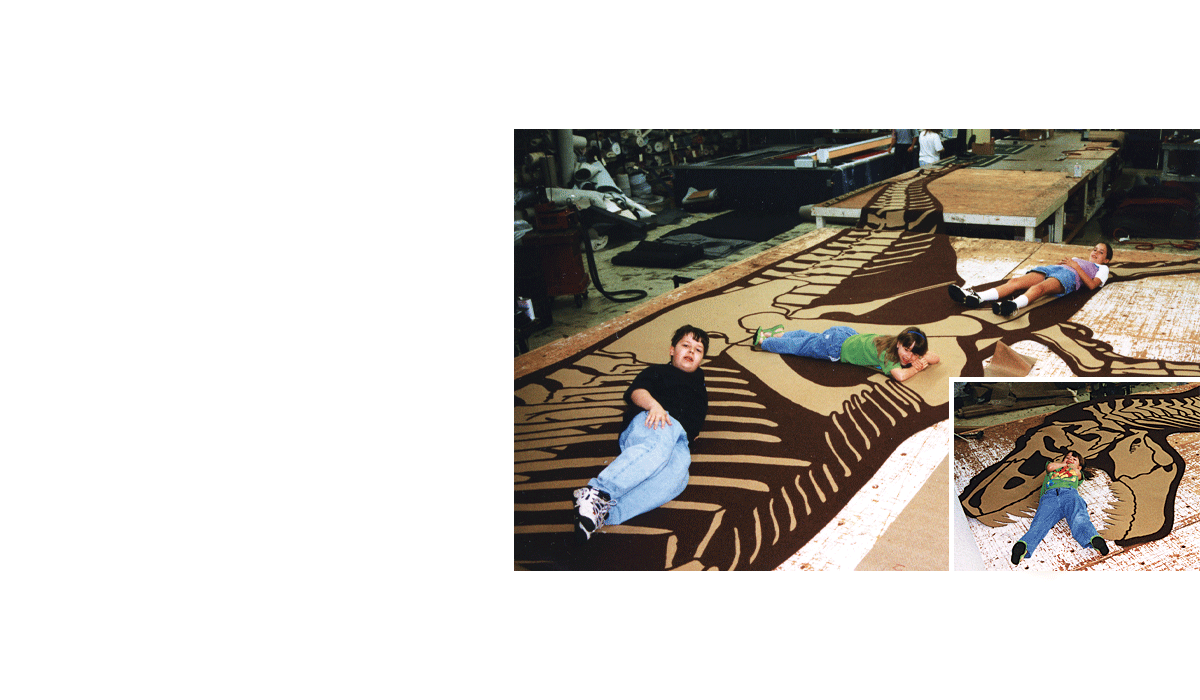 Custom brown and tan inlay for carpet in a museum of a tyrannosaurus rex skeleton with kids